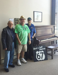 Ace Cannon, Henry Boyce and Sonny Burgess stand beside Porky's piano.