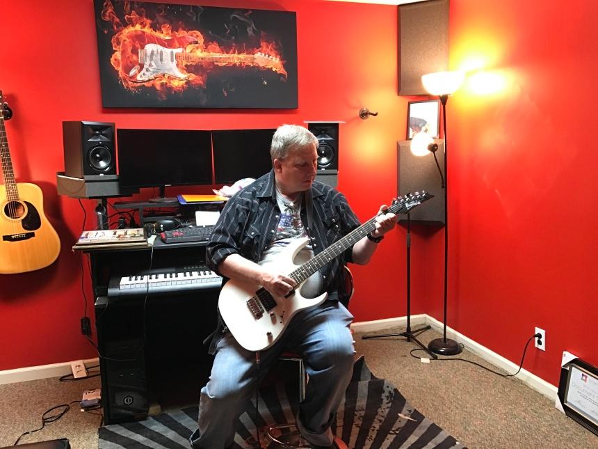 Cameron Todd plays guitar in his studio